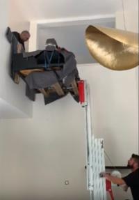 Livraison d'un piano au dessus d'une mezzanine par grue manuelle.